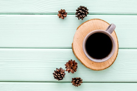 Wooden sawcut. Cup of coffee, wooden stumps and pine cones for blog background on mint green background top view space for text