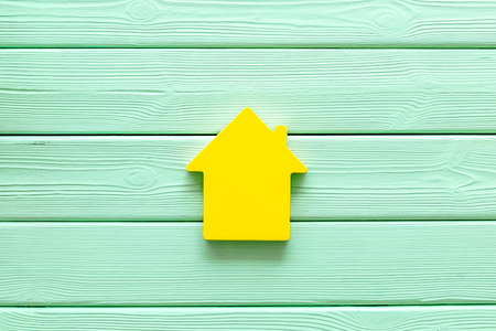 Search for a new house concept with house figure on mint green wooden office desk background top view. Stock Photo - 122256869