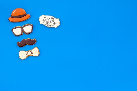 Happy Father Day celebration with cookies in shape of bow tie, moustache, glasses and hat on blue background top view mockup Stock Photo