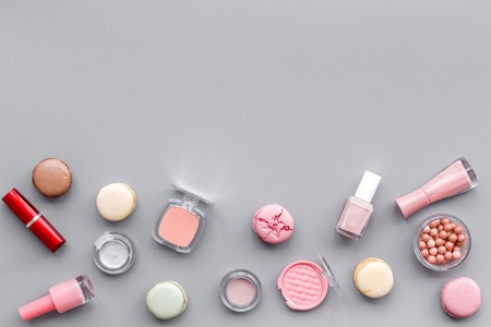 Powder, lipstick, nail polish. Decorative cosmetics for make-up with macaroon cookies on gray tabletop background mockup 免版税图像