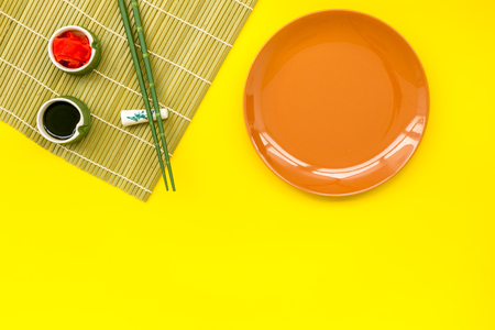 Bamboo sticks, soy sauce, ginger and dishes for sushi and maki cooking on yellow table background top view mockup