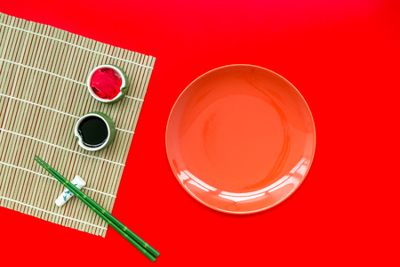 Oriental table set up. Japanese food cooking set with soy sauce, ginger, plate, bamboo sticks for sushi or maki on red background top view copy space