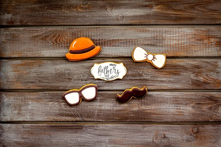 Hat, moustache, glasses, bow tie figures. Design for Father Day celebration party with cookies on wooden background top view mockup