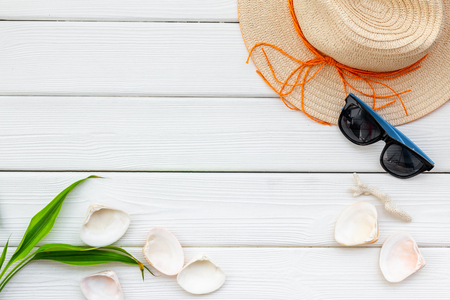 Planning vacation. Summer travelling to the sea with straw hat, sun glasses, shells on white wooden background top view mock up