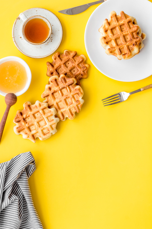 Homemade bakery. Breakfast with Belgian waffles with honey, tea, knife, fork and spoon on yellow table background top view mock up