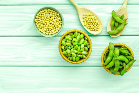 Vegan food concept with green soybeans or edamame in spoon and bowl on mint green wooden desk background top view copy space