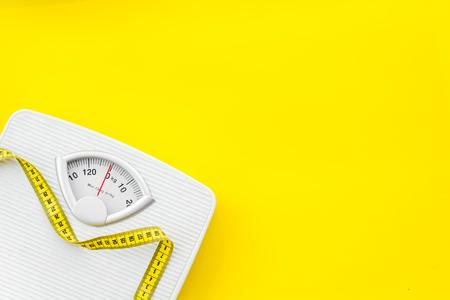 다이어트. 노란색 배경 평면도에서 체중 감량 개념을 위한 욕실 저울 및 측정 테이프 스톡 콘텐츠