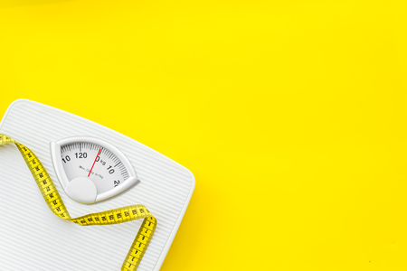Diet. Bathroom scales and measuring tape for weight loss concept on yellow background top view mock up 免版税图像