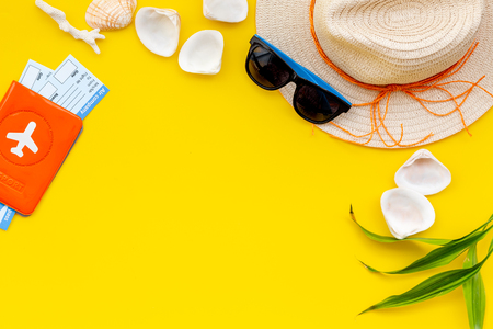 Turistic set. Planning vacation to the seaside with straw hat, sun glasses, shells, passport and tickets on yellow background top view mock-up Stock Photo