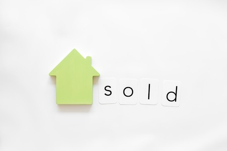 Search for a new house concept with house figure and sold copy on white office desk background top view.