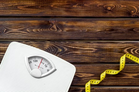 Diet. Bathroom scales and measuring tape for weight loss concept on wooden background top view copy space Фото со стока