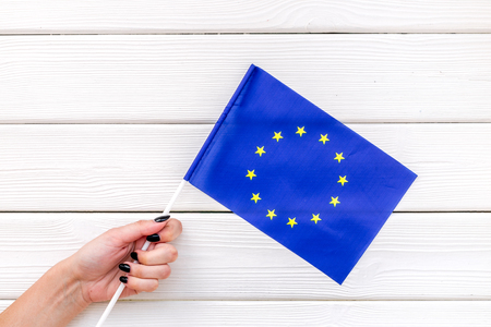 Flag of European Union in hand on white wooden background top view.