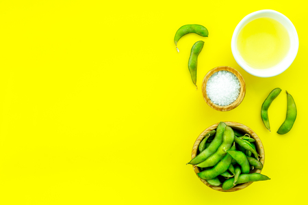 Vegan food concept with green soybeans or edamame and oil on yellow desk background top view copy space Stock Photo