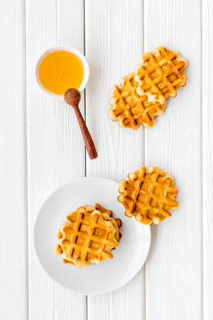 Sweet snack. Viennese waffles. Homemade Belgian waffles with honey on served table on white wooden background top view Zdjęcie Seryjne - 122458338