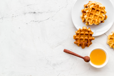 Sweet snack. Viennese waffles. Homemade Belgian waffles with honey on served table on marble background top view copy space
