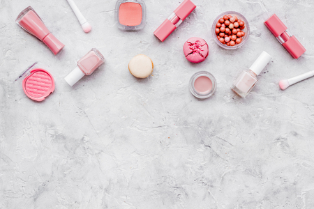 Blusher, lipstick, nail polish. Decorative cosmetics for make-up with macaroon cookies on gray stone tabletop background mock up