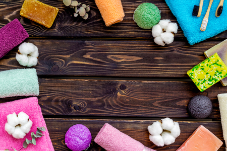 Soap, tooth brush, bath bomb. Spa or resort cosmetics and cotton towels to take bath frame on wooden background top view space for text