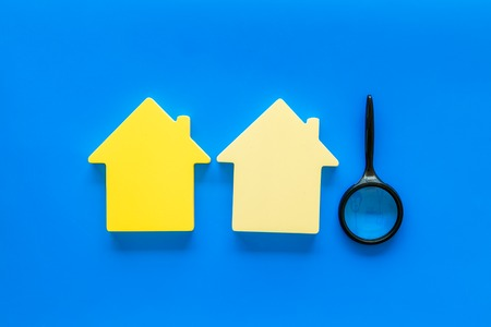 New house purchase. Property insurance concept with house toy and magnifier on blue background top view