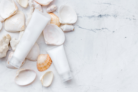 Skin care concept. Cosmetics with Dead Sea minerals. Cream, lotion and shells on marble table background top view copy space 版權商用圖片