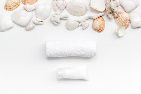Skin care concept. Cosmetics with Dead Sea minerals. Cream, lotion, towel and shells on white table background top view Archivio Fotografico - 122458480