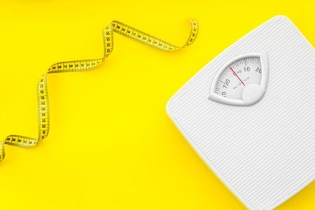 Diät. Personenwaage und Maßband für Gewichtsverlustkonzept auf gelbem Hintergrund Draufsicht