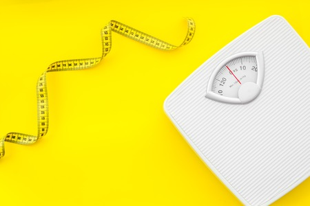 Diet. Bathroom scales and measuring tape for weight loss concept on yellow background top view