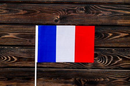 Flag of France on wooden background top view.