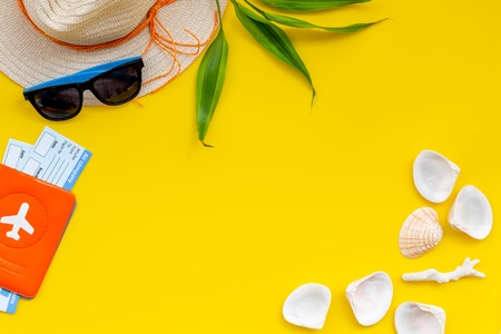 Travel to the seaside. Straw hat, sun glasses, passport and tickets for sea vacation on yellow background top view copy space