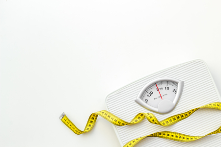 Diet. Bathroom scales and measuring tape for weight loss concept on white background top view space for text 免版税图像 - 122458451