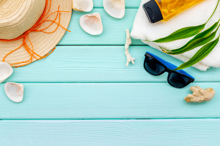 Turistic set. Planning vacation to the seaside with straw hat, sun glasses, shells and sunscreen lotion on mint green wooden background top view mock-up