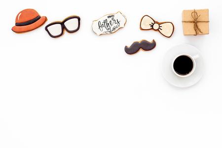 帽子,小胡子,眼镜,蝴蝶结系列。父亲节庆祝党的设计用曲奇饼,礼物盒和咖啡在白色背景顶视图嘲笑