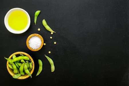 Sport diet food with green soybeans and oil background on black desk top view mockup