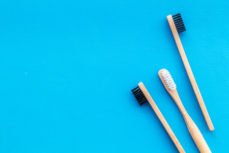 Dental care. Eco materials concept with bamboo tooth brush on blue background top view copy space