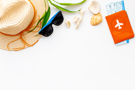 Planning vacation. Summer traveling to the sea with straw hat, sun glasses, shells and tickets and passport on white background top view mock up