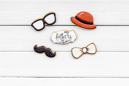 Hat, mustache, glasses, bow tie figures. Design for Father Day celebration party with cookies on white wooden background top view Stockfoto