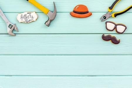 帽子,胡子,眼镜图,修理房屋的仪器。父亲节庆祝党的设计用曲奇饼,礼物盒和咖啡在薄菏绿色木背景顶视图嘲笑
