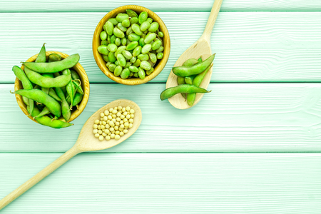 Green soybeans or edamame in spoon and bowl for fresh healthy food on mint green background top view space for text