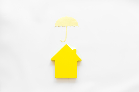 Insurance concept with house figure and umbrella on white background top view