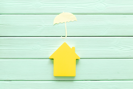 Mortgage credit concept with house and umbrella toys on mint green wooden background top view
