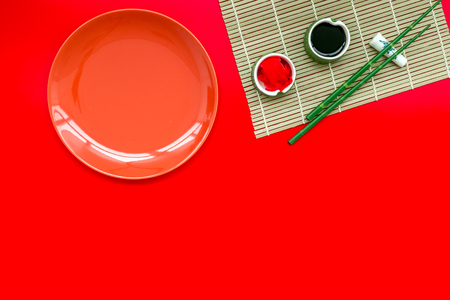 Oriental table set up with plate and bamboo sticks for sushi and maki on red background top view space for text