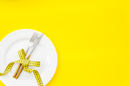 Measuring tape, plate with fork and knife on yellow background top view mockup