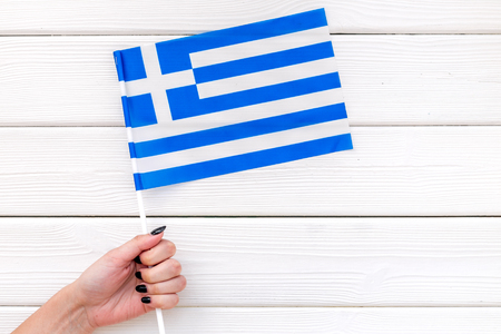 Flag of Greece in hand on white wooden background top view.