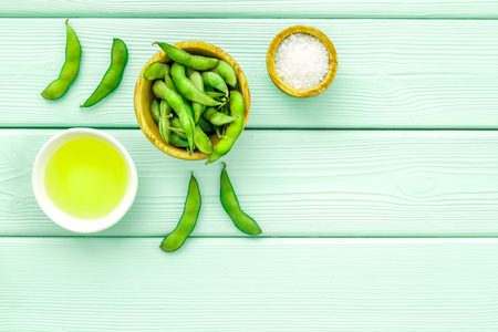 Vegan food concept with green soybeans or edamame and oil on mint green wooden desk background top view copy space