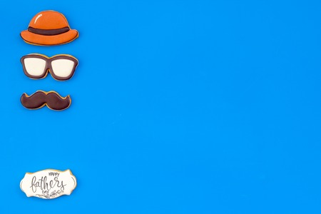 Hat, moustache, glasses figures. Design for Father Day celebration party with cookies on blue background top view mockup