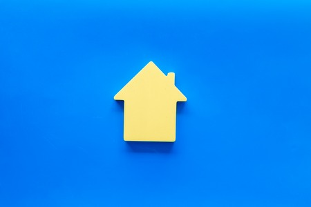 New house purchase. Property insurance concept with house toy on blue background top view Stock Photo