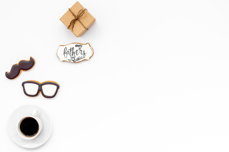 Moustache, glasses, cup of black coffee, box with gift and copy for Happy Father Day celebration party on white background top view copy space