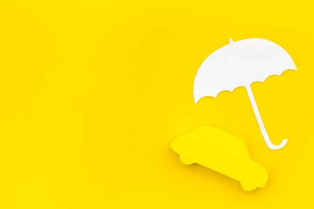 Buying car. Car insurance concept with car and umbrella toys on yellow background top view mockup