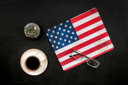 Symbol of Independence and Memorial day of United States of America with flag, glasses and cup of coffee on black background top view