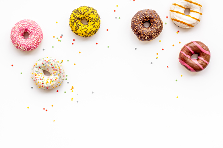 Modern pattern. Glazed decorated donuts for sweet break on white background flat lay copy space