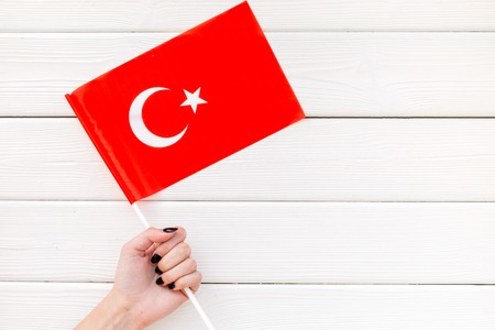 Flag of Turkey in hand on white wooden background top view.